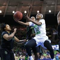 Photo - Notre Dame guard Jewell Loyd (32) drives on Baylor's Khadijiah Cave, left, and Baylor guard Imani Wright (20) in the first half of their NCAA women's college basketball tournament regional final game at the Purcell Pavilion in South Bend, Ind., Monday, March 31, 2014. (AP Photo/Paul Sancya)