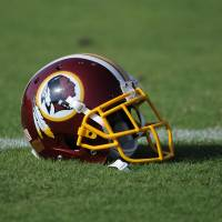 Photo - A Washington Redskins football helmet lies on the field during NFL football minicamp, Wednesday, June 18, 2014, in Ashburn, Va. The U.S. Patent Office ruled Wednesday, June 18, 2014, that the Washington Redskins nickname is