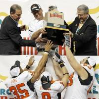 Photo - OSU head coach Mike Gundy hands the trophy to Mathies Long (35), Bo Bowling (9) and Jordan Taormina (63) after the Valero Alamo Bowl college football game between the Oklahoma State University Cowboys ( OSU) and the University of Arizona Wildcats at the Alamodome in San Antonio, Texas, Wednesday, December 29, 2010. OSU won, 36-10. Photo by Nate Billings