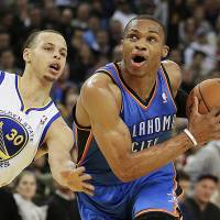 Photo - Oklahoma City Thunder's Russell Westbrook, right, drives past Golden State Warriors' Stephen Curry (30) during the first half of an NBA basketball game, Wednesday, Jan. 23, 2013, in Oakland, Calif. (AP Photo/Ben Margot)