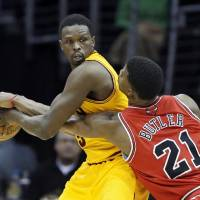 Photo - Chicago Bulls' Jimmy Butler (21) tries to poke the ball away from Cleveland Cavaliers' Luol Deng, of Sudan, in the second quarter of an NBA basketball game Wednesday, Jan. 22, 2014, in Cleveland. (AP Photo/Mark Duncan)