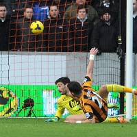 Photo - Hull City's Shane Long, front, scores his side's first goal against Tottenham goalkeeper Hugo Lloris during their English Premier League soccer match at the KC Stadium, Hull, England, Saturday, Feb. 1, 2014. (AP Photo/Anna Gowthorpe, PA Wire)   UNITED KINGDOM OUT  -  NO SALES  -  NO ARCHIVES