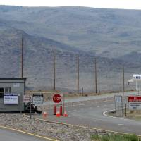 Photo - FILE-This Aug. 1, 2014 file photo shows security guards at the gate to the site Tahoe Reno Industrial Center about 15 miles east of Reno, Nevada. Tesla Motors is considering the site as one of two, or possibly three, finalists where it will build a $5 billion factory to make batteries for a new model of electric car. (AP Photo/Scott Sonner, File)