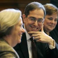 Photo - Christopher L. Eisgruber, center, Princeton's provost for the past nine years, smiles Sunday, April 21, 2013, at Princeton University, as Princeton University president Shirley M. Tilghman announcess Eisgruber will replace her and become the University's 20th president, effective July 1. Eisgruber succeeds Tilghman, who last fall announced her intention to step down at the end of this academic year after completing 12 years in office. (AP Photo/Mel Evans)
