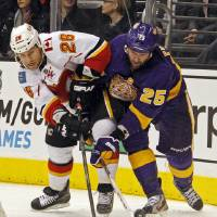 Photo - Los Angeles Kings left winger Dustin Penner (25) and Calgary Flames defenseman Dennis Wideman (26) battle for the puck in the second  period of an NHL hockey game in Los Angeles Saturday, March 9, 2013. (AP Photo/Reed Saxon)
