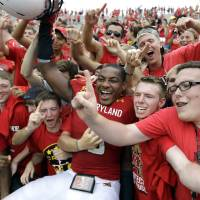 Photo -   Maryland quarterback Demetrius Hartsfield, center, celebrates with fans after defeating William & Mary 7-6 in an NCAA college football game, Saturday, Sept. 1, 2012, in College Park, Md. (AP Photo/Luis M. Alvarez)