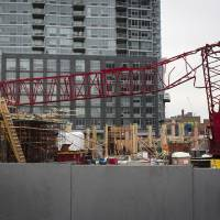 Photo - A mangled crane lies at the construction site in the Queens borough of New York where it collapsed, Wednesday, Jan. 9, 2013. The Fire Department of New York says the 200-foot crane collapsed onto a building under construction, injuring seven people, three of them seriously. (AP Photo/John Minchillo)