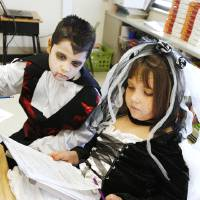 Photo - Second-graders Alex Rodas, 7, and Autumn McGinty, 8, are dressed as a vampire and bride of Frankenstein while doing class work at Hayes Elementary.  Photos by PAUL B. SOUTHERLAND, THE OKLAHOMAN