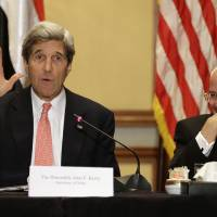 Photo - U.S. Secretary of State John Kerry, left, waves while ending a statement to the media, next to Mohammed Kassem, of World Trading Company, during a meeting with business leaders in Cairo, Egypt on Saturday, March 2, 2013. Cairo is the sixth leg of Kerry's first official overseas trip and begins the Middle East portion of his nine-day journey. (AP Photo/Jacquelyn Martin, Pool)