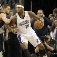 Photo - Sacramento Kings center DeMarcus Cousins, right, goes to the basket against Toronto Raptors center Jonas Valanciunas, of Lithuania,  during the first quarter of an NBA basketball game in Sacramento, Calif., Wednesday, Dec. 5, 2012. (AP Photo/Rich Pedroncelli)