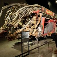 Photo - The remains of Fire Dept. of New York Ladder Company 3's truck are displayed at the National Sept. 11 Memorial Museum, Wednesday, May 14, 2014, in New York. The museum is a monument to how the Sept. 11 terror attacks shaped history, from its heart-wrenching artifacts to the underground space that houses them amid the remnants of the fallen twin towers' foundations. It also reflects the complexity of crafting a public understanding of the terrorist attacks and reconceiving ground zero.  (AP Photo)