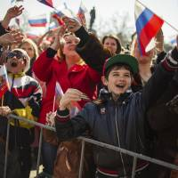 Photo - People wave Russian flags as they gather at a square to watch a televised address by Russian President Vladimir Putin to the Federation Council, in Sevastopol, Crimea, Tuesday, March 18, 2014. Putin on Tuesday fiercely defended Russia's move to annex Crimea saying Crimea's vote on Sunday to join Russia was in line with