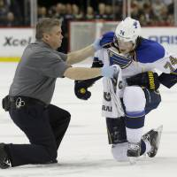 Photo - St. Louis Blues right wing T.J. Oshie (74) tries to get up with help from a trainer but can't after being injured during the second period of an NHL hockey game against the Minnesota Wild in St. Paul, Minn., Thursday, April 10, 2014. (AP Photo/Ann Heisenfelt)