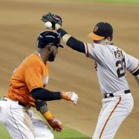 Photo - Miami Marlins' Marcell Ozuna, left, reaches first base on an error by San Francisco Giants first baseman Buster Posey, right, during the fourth inning of a baseball game, Sunday, July 20, 2014 in Miami. (AP Photo/Wilfredo Lee)