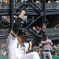 Photo - Pittsburgh Pirates' Russell Martin scores from second on a single by teammate Clint Barmes during the second inning of a baseball game against the Atlanta Braves in Pittsburgh, Sunday, April 21, 2013. (AP Photo/Gene J. Puskar)