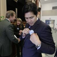 Photo - Sen. Kevin de Leon, D-Los Angeles, puts on a sticker for his proposed bill, SB39,  to fund energy efficiency projects at schools in California's poorest communities, before a news conference at Mark Twin Elementary School in Sacramento, Calif., Tuesday, Dec. 4, 2012.  The bill would use money from last month's voter approved initiative, Proposition 39, that requires  $500 million for five years be used for clean air project.(AP Photo/Rich Pedroncelli)