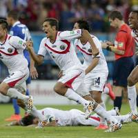 Photo - Costa Rica players react after Michael Umana scored during a shootout after regulation time in the World Cup round of 16 soccer match between Costa Rica and Greece at the Arena Pernambuco in Recife, Brazil, Sunday, June 29, 2014. Costa Rica defeated Greece 5-3 in penalty shootouts after a 1-1 tie. (AP Photo/Petr David Josek)
