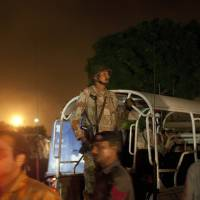 Photo - Pakistani security troops rush to Karachi airport terminal following attacks by unknown gunmen on Sunday night, June 8, 2014, in Pakistan. Gunmen stormed an airport terminal used for VIPs and cargo in Pakistan's largest city on Sunday night, killing and wounding scores of people, officials said. (AP Photo/Shakil Adil)