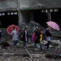 Photo -   Palestinian schoolchildren walk in debris by a damaged school in Gaza City, Saturday, Nov. 24, 2012. Schools in Gaza opened Saturday for the first time since the truce, which calls for an end to Gaza rocket fire on Israel and Israeli airstrikes on Gaza, came after eight days of cross-border fighting, the bloodiest between Israel and Hamas in four years. The school was damaged when Israeli forces struck on a nearby building. (AP Photo/Bernat Armangue)