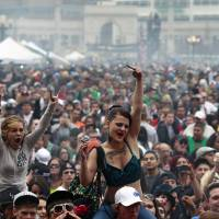 Photo - FILE - In this April 20, 2013 file photo, members of a crowd numbering tens of thousands smoke marijuana and listen to live music, at the Denver 420 pro-marijuana rally at Civic Center Park in Denver. The U.S. government said Thursday, Aug. 29, 2013 that the federal government will not make it a priority to block marijuana legalization in Colorado or Washington or close down recreational marijuana stores, so long as the stores abide by state regulations. (AP Photo/Brennan Linsley, File)