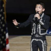 Photo - Sebastien De la Cruz sings the national anthem before Game 4 of the NBA Finals basketball series between the San Antonio Spurs and the Miami Heat, Thursday, June 13, 2013, in San Antonio. (AP Photo/David J. Phillip)