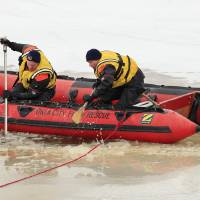 Photo - Oklahoma City Fire Department divers check a pond Friday behind businesses in the 12300 block of Market Drive near NE 122 Street and Kelley Ave. in Oklahoma City. Footprints were seen going to and from a hole in the ice on the pond and a glove and beanie found near the hole. The pond is 7 feet deep where the hole was. Photo by Paul B. Southerland, The Oklahoman  PAUL B. SOUTHERLAND