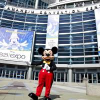 Photo - FILE - In this Sept. 9, 2009 handout photo released by Disney, Mickey Mouse stands in front of the Anaheim Convention Center in preparation for the Disney D23 Expo in Anaheim, Calif.  The Walt Disney Co. is cracking open the vault, rolling out the red carpet and pulling back the curtain for more than 45,000 expected fans at this weekend's D23 Expo, Aug. 9-11, 2013, a three-event celebration of all things Disney at the Anaheim Convention Center.  On the animation front, the studio will showcase Walt Disney Animation Studios' computer-generated adventure