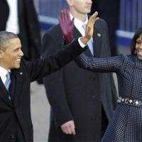 Photo - President Barack Obama and first lady Michelle Obama wave as they arrive in front of the White House during the Inaugural parade in Washington, Monday, Jan. 21, 2013.  Thousands marched during the 57th presidential inauguration parade after the ceremonial swearing-in of Obama. (AP Photo/Gerald Herbert)