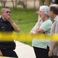 Photo - People stand with a law enforcement officer near the scene of a shooting Wednesday, July 9, 2014, in Spring, Texas. A Harris County Sheriff's Office statement says precinct deputy constables were called to the house about 6 p.m. Wednesday and found two adults and three children dead. Another child later died at a hospital. (AP Photo/Houston Chronicle, Brett Coomer)