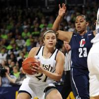 Photo - Notre Dame guard Kayla McBride, left, throws a pass around Connecticut guard Kaleena Mosqueda-Lewis during the first half of an NCAA college basketball game, Monday, March 4, 2013, in South Bend, Ind. (AP Photo/Joe Raymond)