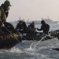Photo - Divers look for people believed to have been trapped in the sunken ferry Sewol in the water off the southern coast near Jindo, south of Seoul, South Korea, Wednesday, April 23, 2014. The grim work of recovering bodies from the submerged South Korea ferry proceeded rapidly Wednesday, with the official death toll reaching over 140, though a government official said divers must now rip through cabin walls to retrieve more victims. (AP Photo/Yonhap)  KOREA OUT