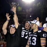 Photo - FILE - This Jan. 1, 2011 file photo shows TCU head coach Gary Patterson holding up the Rose Bowl Trophy after defeating Wisconsin in the Rose Bowl NCAA college football game, in Pasadena, Calif. People with knowledge of the decision say Big 12 leaders have agreed to invite TCU to join the fractured league as early as the 2012 football season. The offer to TCU will be extended sometime in the next few days, according to two people with ties to the Big 12. The people spoke only on condition of anonymity because the league has not announced the decision. (AP Photo/Mark J. Terrill, File) ORG XMIT: NY159