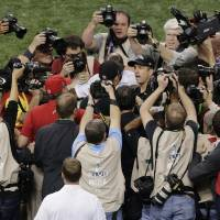 Photo - Photographers surround Baltimore Ravens head coach John Harbaugh, right, and San Francisco 49ers head coach Jim Harbaugh as they shake hands after the NFL Super Bowl XLVII football game, Sunday, Feb. 3, 2013, in New Orleans. The Ravens won 34-31. (AP Photo/Charlie Riedel)