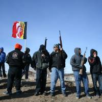 Photo - Members of the American Indian Movement stand near the Wounded Knee Massacre Monument, Wednesday, Feb. 27, 2013 in Wounded Knee, S.D. Wednesday marked the 40th anniversary of the start of the 71-day occupation in the village of Wounded Knee on the Pine Ridge Indian Reservation. Hundreds of AIM members and other supporters turned out for a day of ceremonies to commemorate the anniversary of the fatal standoff that drew national attention to the impoverished reservation and the plight of local tribes. (AP Photo/Kristi Eaton)