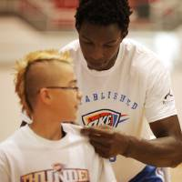 Photo - Hasheem Thabeet, center for the Oklahoma City Thunder, autographs the back of Joseph Nicolle, 13 of Moore, at the Thunder basketball camp at Carl Albert High School in Midwest City on June 25, 2013. Photo by KT KING, The Oklahoman