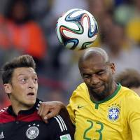 Photo - Germany's Mesut Ozil, left, and Brazil's Maicon go for a header during the World Cup semifinal soccer match between Brazil and Germany at the Mineirao Stadium in Belo Horizonte, Brazil, Tuesday, July 8, 2014. (AP Photo/Frank Augstein)