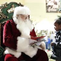 Photo - Santa talks with Narilyn Wooden, 4, on Tuesday during a tree-lighting ceremony at The Outlet Shoppes at Oklahoma City. PHOTOS BY SARAH PHIPPS, THE OKLAHOMAN