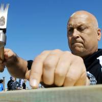 Photo - Baseball Hall of Famer Cal Ripken Jr. hammers a nail as he helps build a Habitat for Humanity home in Joplin, Mo. AP PHOTOS