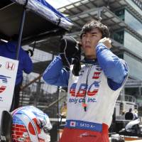 Photo - Takuma Sato, of Japan, removes his earplugs after driving during practice for the Indianapolis 500 IndyCar auto race at the Indianapolis Motor Speedway in Indianapolis, Monday, May 19, 2014. (AP Photo/Michael Conroy)