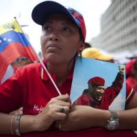 Photo - A woman holds a picture of Venezuela's President Hugo Chavez and the country's national flag during an event commemorating the violent street protests of 1989 known as the
