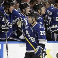 Photo - Tampa Bay Lightning right wing Martin St. Louis (26) gets high fives from the bench after his goal against the Toronto Maple Leafs during the third period of an NHL hockey game Wednesday, April 24, 2013, in Tampa, Fla. (AP Photo/Chris O'Meara)