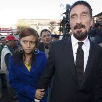 Photo - Software company founder John McAfee, right, accompanied by his girlfriend