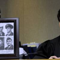 Photo - Judge Karen Khalil sits beside a framed photo of her six uncles that served in the military at Redford District Court (17th District) in Redford on Nov. 5, 2012. Veterans participate in special veterans court aimed at helping veterans who have been charged with drug and non-violent offenses. The specialized courts are a growing trend in courts across the country since Buffalo, N.Y. first started its vets court a few years ago. (AP Photo/The Detroit News, David Coates)