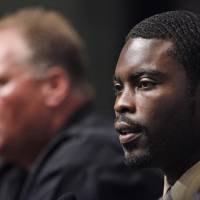 Photo -   	 Michael Vick is along with seen Philadelphia Eagles head coach Andy Reid during a news conference in Philadelphia, Friday, Aug. 14, 2009. Vick is back in the NFL, landing a job with the Philadelphia Eagles. Looking to add a new dimension to their offense, the Philadelphia Eagles gave Vick a one-year deal with an option for a second year. (AP Photo/Matt Rourke)