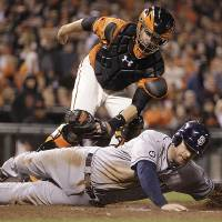 Photo -   San Diego Padres' Chase Headley is tagged out at home plate by San Francisco Giants catcher Buster Posey (top) in the sixth inning of a baseball game Friday, Sept 21, 2012, in San Francisco. Headley attempted to score on a double by Yasmani Grandal. (AP Photo/Ben Margot)
