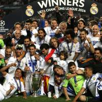 Photo - Real Madrid team pose with theChampion League trophy, after winning the Champion League title, against Atletico Madrid 4-1, in Lisbon, Portugal, Saturday, May 24, 2014. (AP Photo/Daniel Ochoa de Olza)
