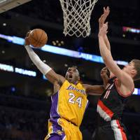 Photo - Los Angeles Lakers guard Kobe Bryant, left, goes up for a shot as Portland Trail Blazers center Meyers Leonard defends during the first half of their NBA basketball game, Friday, Feb. 22, 2013, in Los Angeles. (AP Photo/Mark J. Terrill)