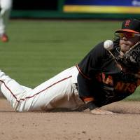Photo - San Francisco Giants shortstop Brandon Crawford throws Colorado Rockies' Ryan Wheeler out at second during the fifth inning of an exhibition baseball game in Scottsdale, Ariz., Wednesday, March 26, 2014. (AP Photo/Chris Carlson)