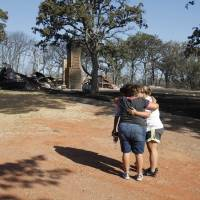 Photo - The Grigg family hugs Saturday as they gather to see for the first time the damage from Friday's wildfire in Slaughterville. Photo by Steve Sisney, The Oklahoman