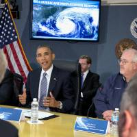 Photo - President Barack Obama speaks at Federal Emergency Management Agency (FEMA) headquarters in Washington, Friday, May 30, 2014, during a hurricane preparedness meeting. at right is Federal Emergency Management Agency (FEMA) administrator Craig Fugate. (AP Photo/Carolyn Kaster)